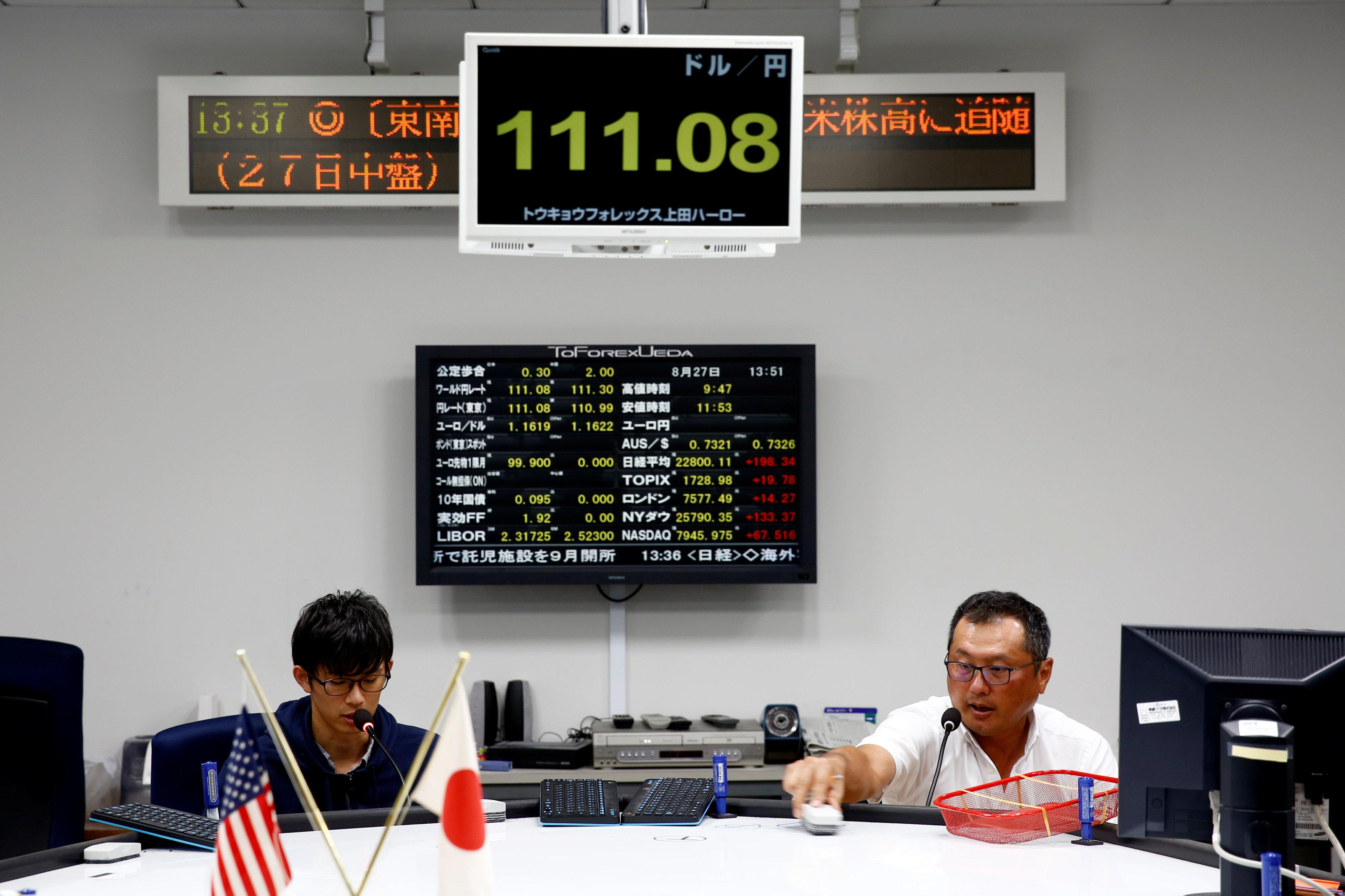 Tsutomu Fukasawa (R), a foreign exchange dealer, works with a colleague at Tokyo Forex & Ueda Harlow, almost 10 years on from the collapse of Lehman Brothers, in Tokyo, Japan, August 27, 2018.  Kim Kyung-Hoon