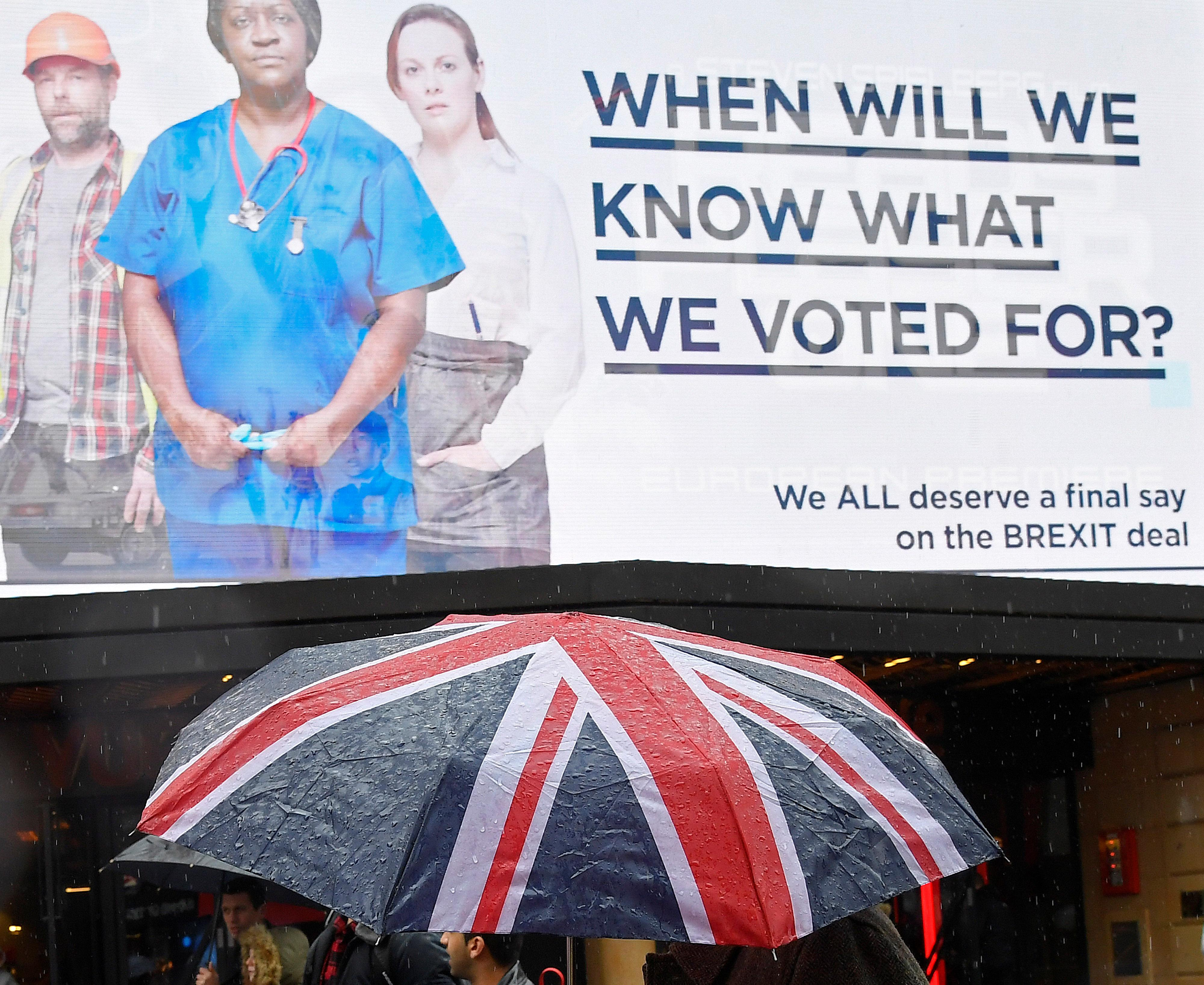 A pedestrian shields himself with a British union flag umbrella as he passes a billboard with a Brexit related campaign slogan in Leicester Square, London, Britain, March 29, 2018. Toby Melville