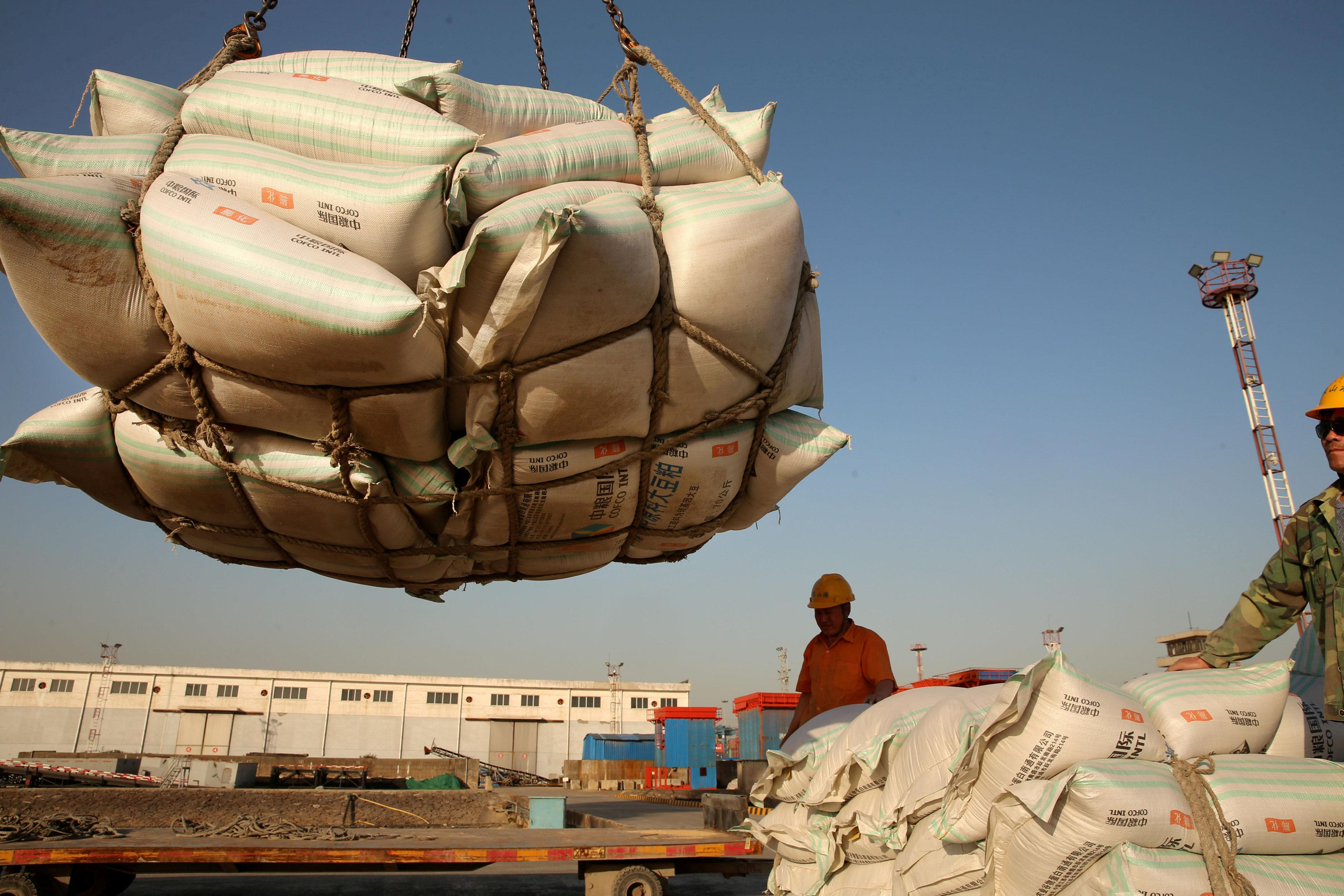 Workers transport imported soybean products at a port in Nantong, Jiangsu province, China April 9, 2018. Picture taken April 9, 2018. Stringer