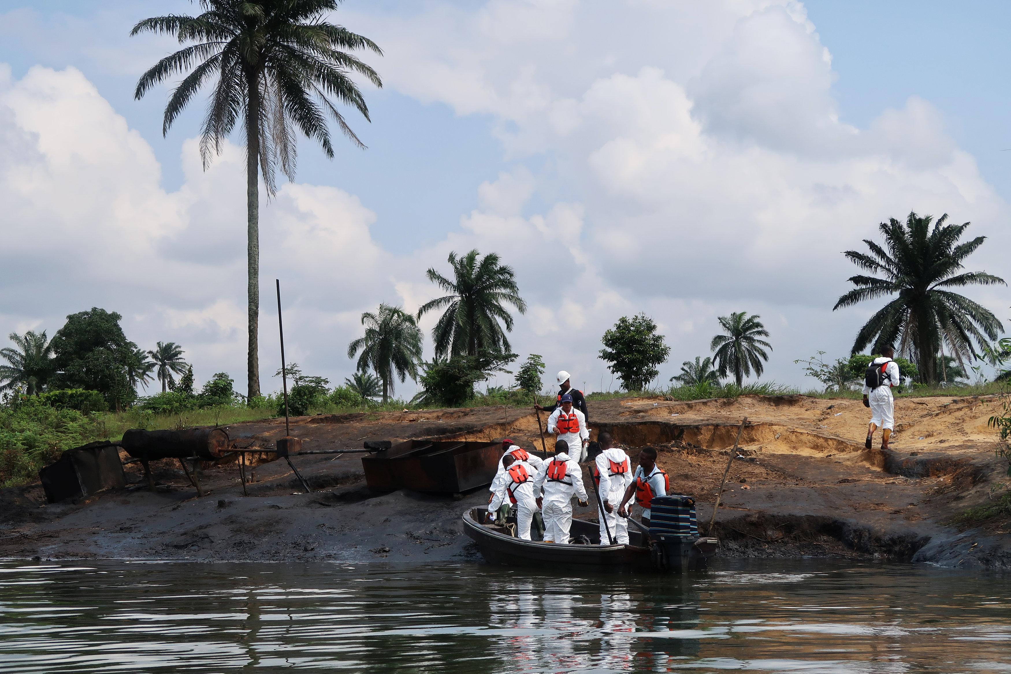 A team of the joint task force, part of the Bodo oil spill clean-up operation, disembarks from a boat at the site of an illegal refinery near the village of Bodo in the Niger Delta, Nigeria August 2, 2018.  Ron Bousso