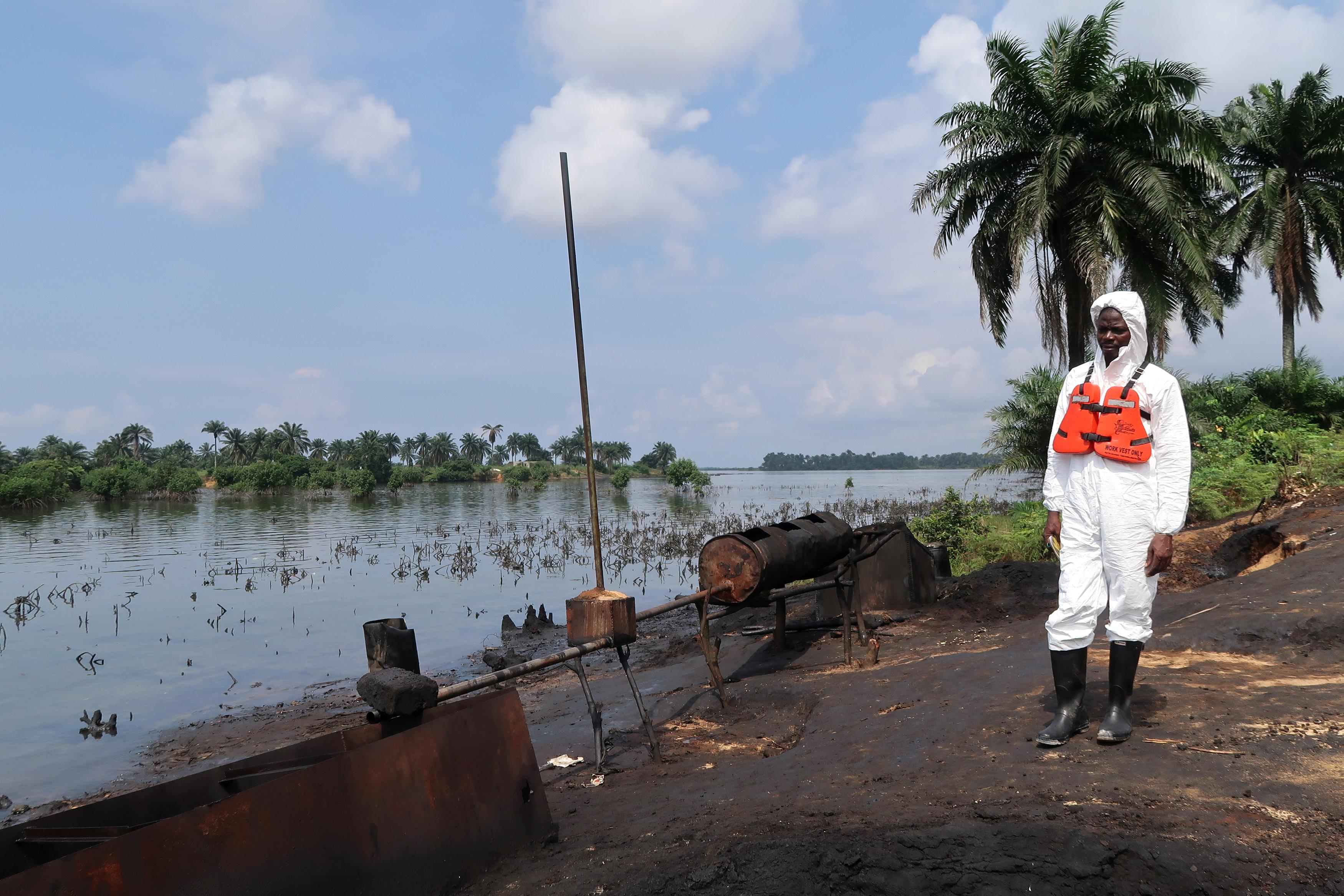 A member of the joint task force, part of the Bodo oil spill clean-up operation, stands near the site of an illegal refinery near the village of Bodo in the Niger Delta, Nigeria August 2, 2018. Picture taken August 2, 2018.   Ron Bousso