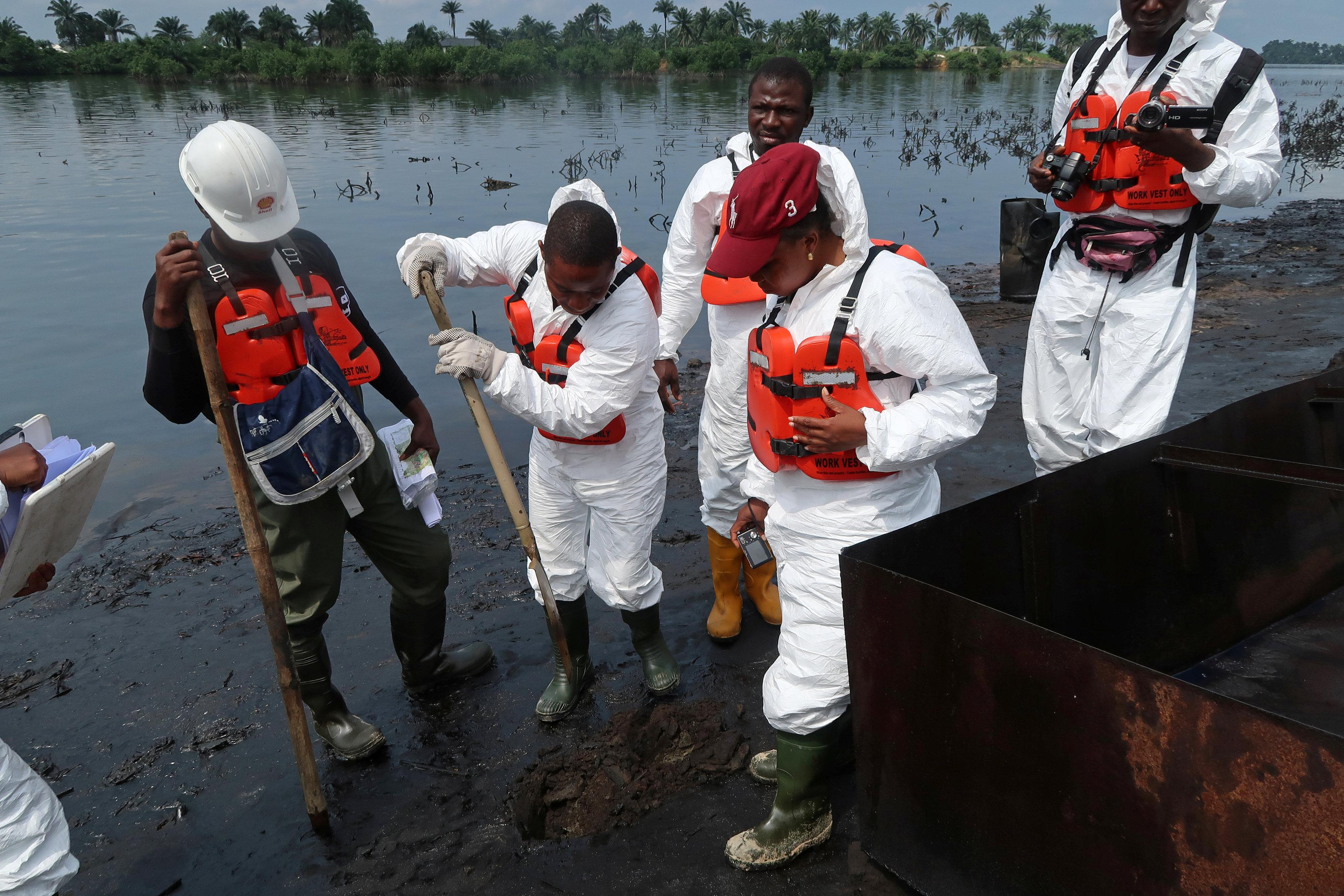 Members of the joint task force, part of the Bodo oil spill clean-up operation, inspect the site of an illegal refinery near the village of Bodo in the Niger Delta, Nigeria August 2, 2018.   Ron Bousso