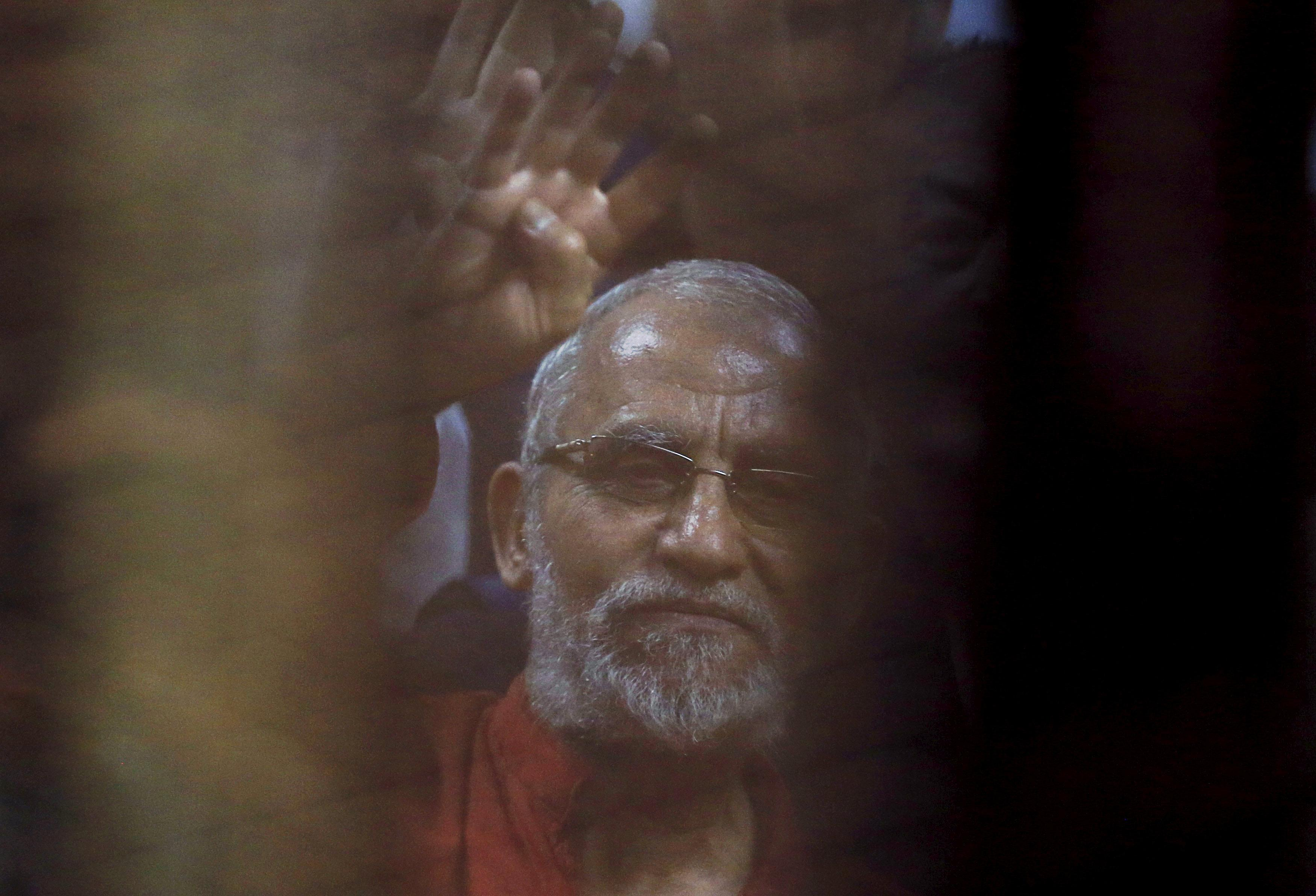 Muslim Brotherhood's Supreme Guide Mohamed Badie waves with the Rabaa sign, symbolizing support for the Muslim Brotherhood, with other brotherhood members at a court in the outskirts of Cairo, Egypt, June 2, 2015.  Amr Abdallah Dalsh