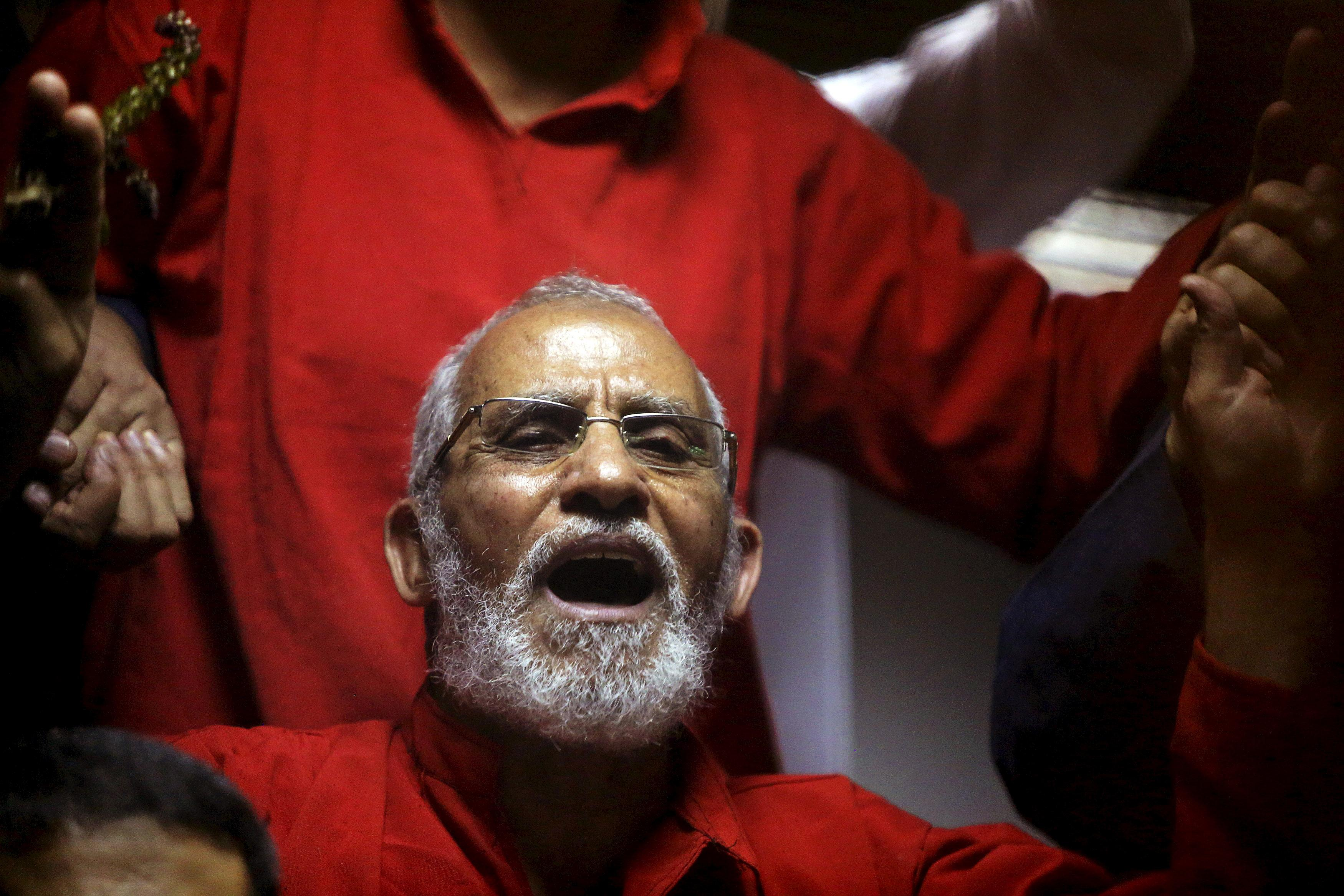 Muslim Brotherhood's Supreme Guide Mohamed Badie (C) reacts with other brotherhood members at a court in the outskirts of Cairo, Egypt May 16, 2015. Mohamed Abd El Ghany