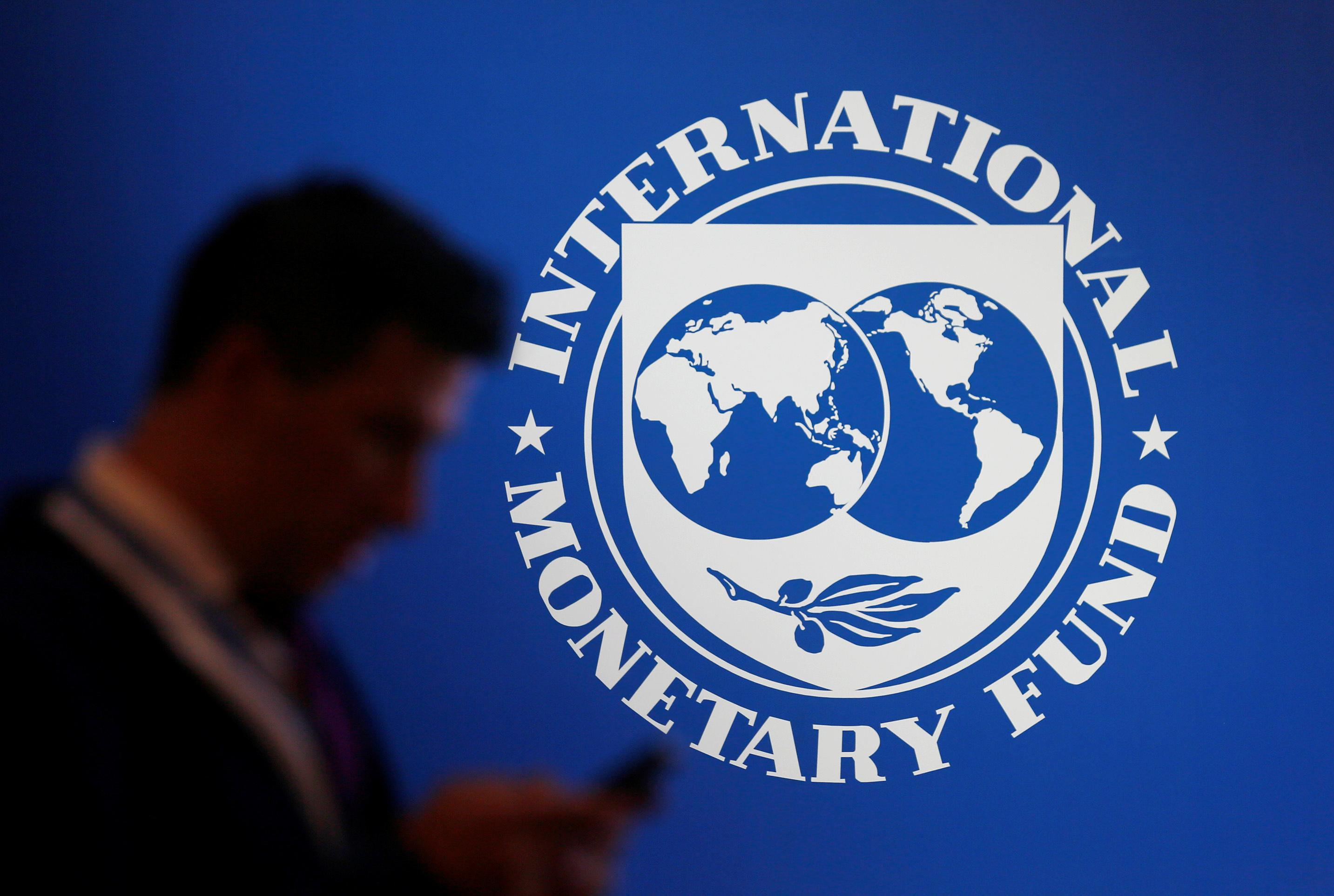 A participant stands near a logo of IMF at the International Monetary Fund - World Bank Annual Meeting 2018 in Nusa Dua, Bali, Indonesia, October 12, 2018. Johannes P. Christo