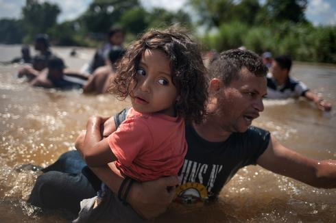 Migrant caravan crosses river into Mexico