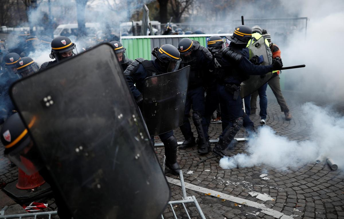 French police clash violently with protesters on Champs Elysees...