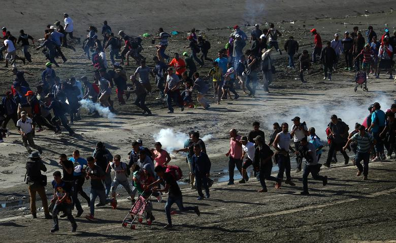 Migrants run from tear gas released by U.S. border patrol, near the border fence between Mexico and the United States in Tijuana, Mexico, November 25, 2018. REUTERS/Hannah McKay