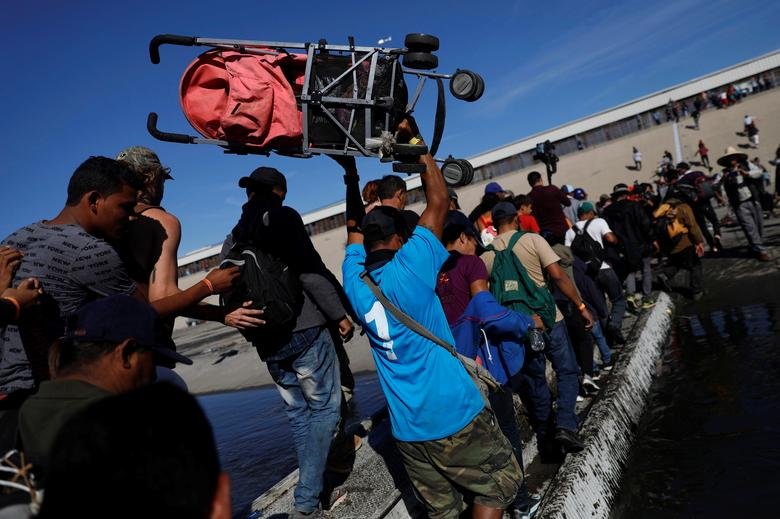 Migrants make their way across Tijuana river near the border wall between the U.S. and Mexico in Tijuana, Mexico November 25, 2018. REUTERS/Edgard Garrido