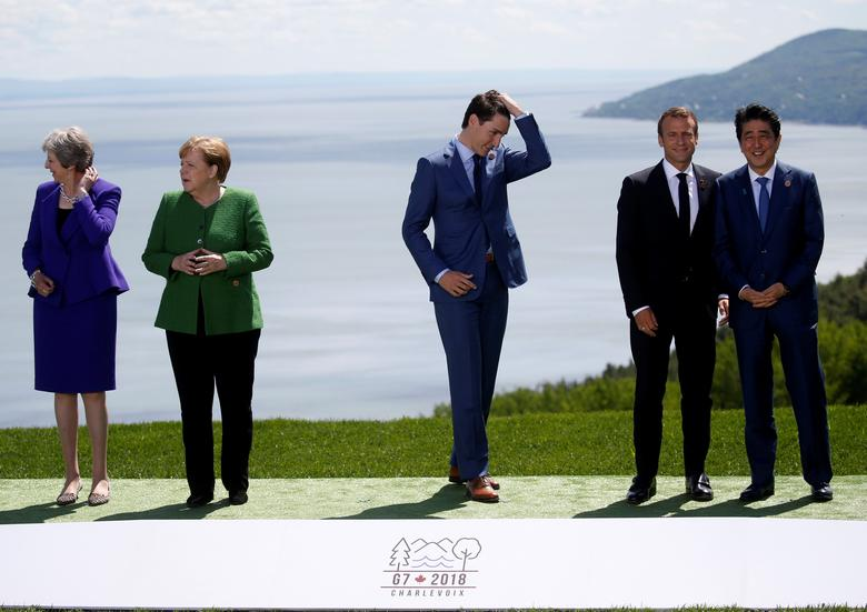 British Prime Minister Theresa May, German Chancellor Angela Merkel, Canada's Prime Minister Justin Trudeau, France's President Emmanuel Macron and Japanese Prime Minister Shinzo Abe wait for U.S. President Donald Trump to join them for a family photo at the G7 Summit in Charlevoix, Quebec, Canada, June 8.       REUTERS/Leah Millis