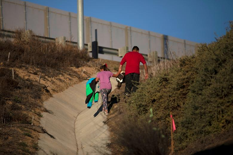 Tony Mauricio Arita, 33 and his daughter Andrea Nicole, 10, climb a hill after crawling through a hole under a border wall to cross illegally from Mexico to the U.S, photographed through the border wall from Tijuana, Mexico, December 4, 2018. REUTERS/Alkis Konstantinidis