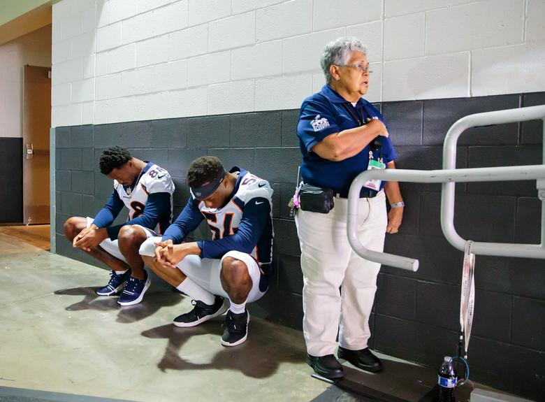 A stadium security guard stands with her hand over her heart as Denver Broncos linebacker Brandon Marshall (54) and wide receiver Demaryius Thomas (88) sit in silent protest during the national anthem prior to their preseason game against the Arizona Cardinals, August 30, 2018.     Mark J. Rebilas-USA TODAY Sports