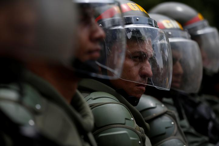 Venezuelan National Guards stand guard during clashes with opposition...