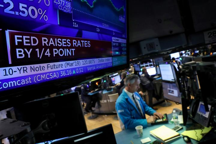 FILE PHOTO: A screen displays the headlines that the U.S. Federal Reserve...