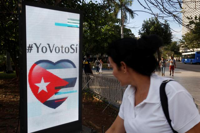 A woman passes by a screen displaying images promoting the vote for ''yes'' for the constitutional referendum, in Havana, Cuba, February 5, 2019. Picture taken on February 5, 2019. REUTERS/Stringer