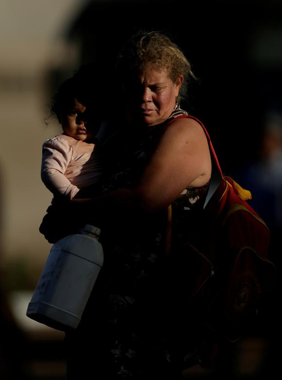 A woman holding a child waits to fill her canister with fuel at a gas station on the outskirts of Brasilia, Brazil May 29, 2018. REUTERS/Ueslei Marcelino