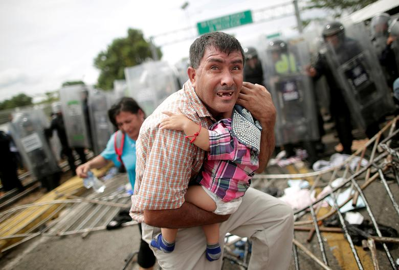 A Honduran migrant protects his child after fellow migrants, part of a caravan trying to reach the U.S., stormed a border checkpoint in Guatemala, in Ciudad Hidalgo, Mexico October 19, 2018. REUTERS/Ueslei Marcelino