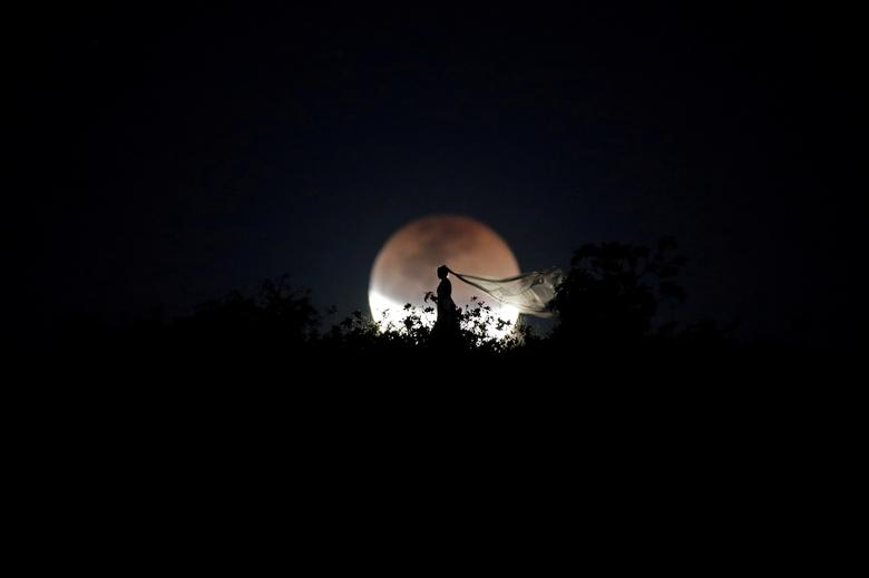 A bride poses for a photo during a total lunar eclipse in Brasilia, Brazil, July 27, 2018. REUTERS/Ueslei Marcelino