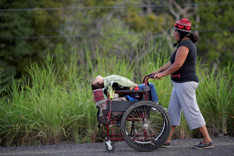 A migrant woman, traveling with a caravan of thousands from Central America, pushes her son in a wheelchair as she walks along the highway to Juchitan from Santiago Niltepec, Mexico, October 30, 2018. REUTERS/Ueslei Marcelino