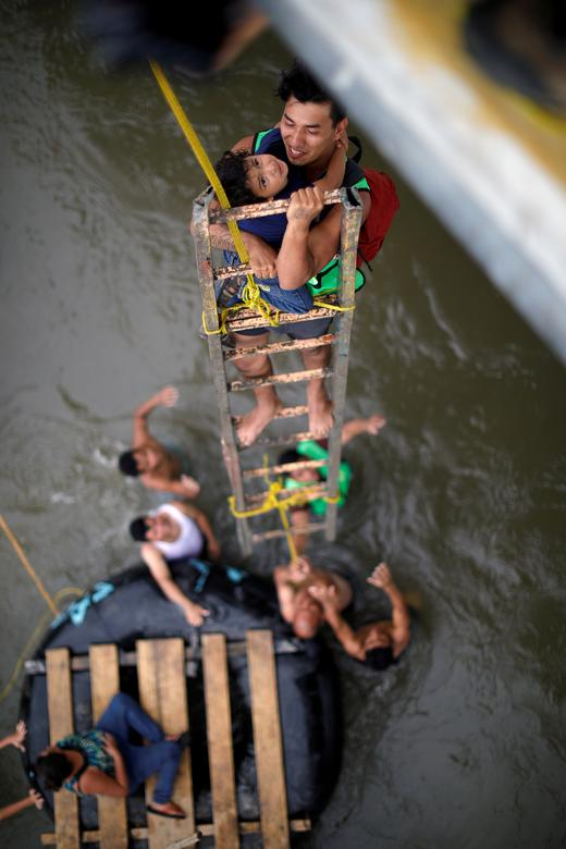 Central American migrants, part of a caravan trying to reach the U.S., use a provisional ladder to climb down from the bridge that connects Mexico and Guatemala, in Ciudad Hidalgo, Mexico, October 20, 2018. REUTERS/Ueslei Marcelino