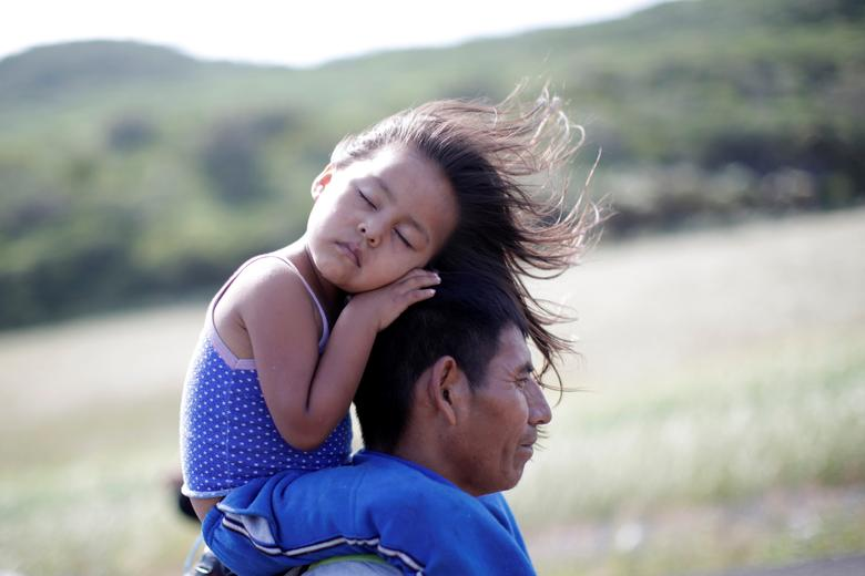 Rosendo Noviega, a 38-year-old migrant from Guatemala, part of a caravan of thousands from Central America en route to the United States, holds his daughter Belinda Izabel as he walks along the highway to Juchitan from Santiago Niltepec, Mexico, October 30, 2018. REUTERS/Ueslei Marcelino