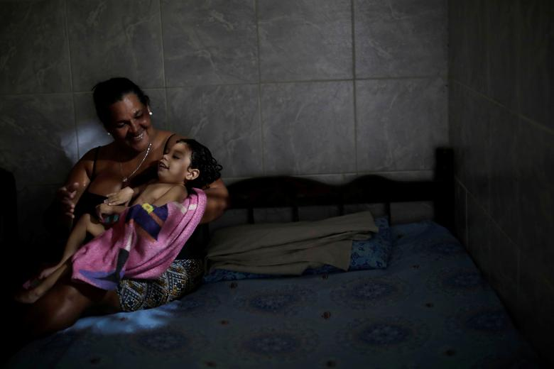 "Silvina da Silva poses with her 2-year-old granddaughter Ana Sophia, who was born with microcephaly, at their house in Olinda, Brazil, August 7, 2018. Ana Sophia's mother Gabriela had planned to finish high school and study physical therapy. Now, she spends her days caring for her child. Her husband left shortly after Ana Sophia's birth. He could not accept their child's condition, Gabriela says, and does not pay child support. ""I went into depression and my family helped me,"" she said. ""If it was not for them, I would have gone crazy."" Today, some relatives give moral support and Ana Sophia's paternal grandmother helps with her day-to-day care. REUTERS/Ueslei Marcelino"