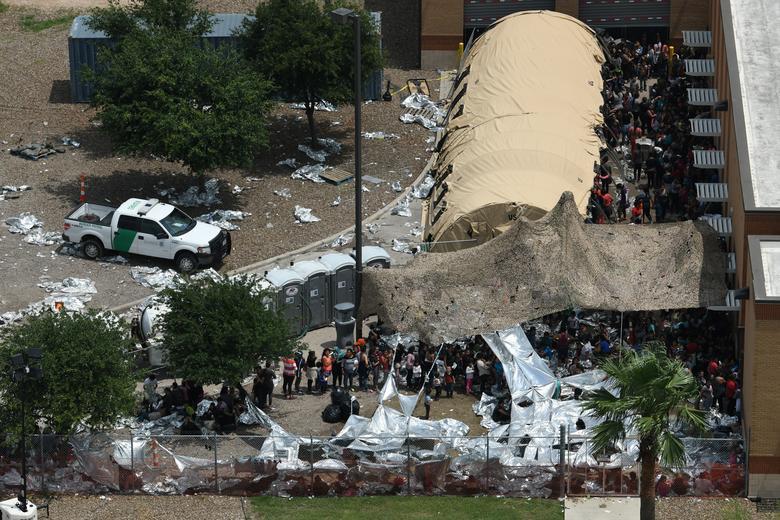 Los migrantes se ven fuera de la Estación McAllen de la Patrulla Fronteriza de los EE. UU. En un campamento improvisado en McAllen, Texas. REUTERS / Loren Elliott
