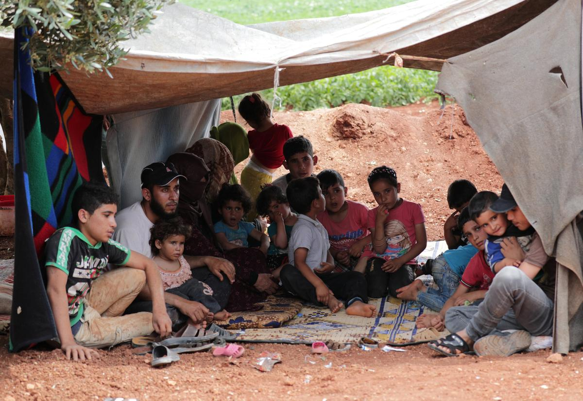 Fleeing into the fields, a family runs from Idlib attacks