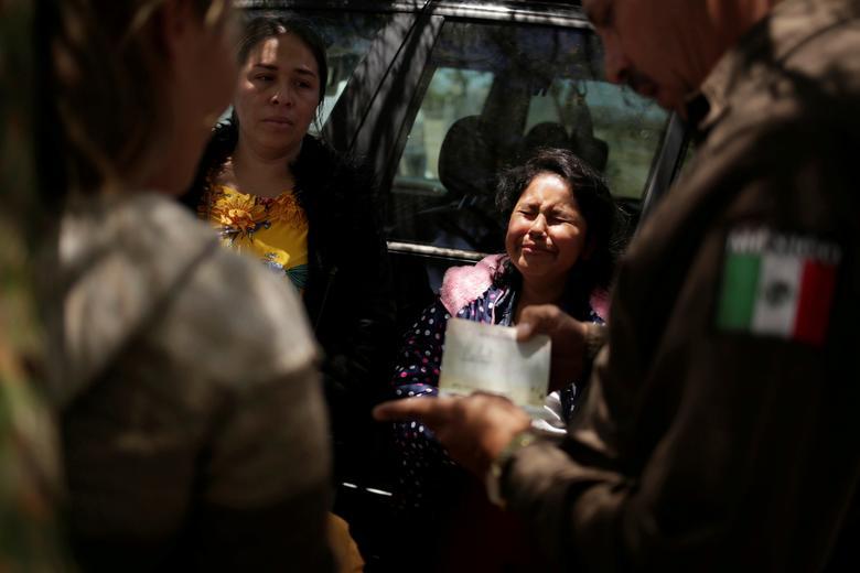 Una joven de Nicaragua reacciona cuando un miembro de la Guardia Nacional de México mira los papeles después de detenerla a ella, a su madre y a otra mujer, mientras intentaban cruzar ilegalmente la frontera entre EE. UU. Y México en Ciudad Juárez, México, el 21 de junio. México no ha utilizado tradicionalmente Las fuerzas de seguridad para detener a los ciudadanos extranjeros indocumentados que salen del país a Estados Unidos, y las fotografías de policías militarizados que capturan a mujeres centroamericanas y cubanas en la frontera en los últimos días han sido criticadas. REUTERS / Jose Luis Gonzalez
