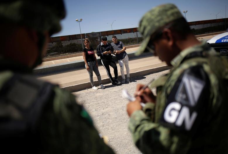 """Miembros de la Guardia Nacional de México detienen a inmigrantes cubanos cuando intentaban cruzar ilegalmente la frontera entre los Estados Unidos y México, en Ciudad Juárez, el 21 de junio. """"En la parte norte del país tenemos un despliegue total de 14,000, casi 15,000 unidades entre """"La Guardia Nacional y el Ejército"""", dijo Sandoval en una conferencia de prensa regular. """"Si lo dejáramos completamente en manos del Instituto Nacional de Migración, no sería posible"""", agregó. """"Es por eso que estamos brindando apoyo, es una estrategia que se persigue en ambas fronteras"""". REUTERS / Jose Luis Gonzalez"""
