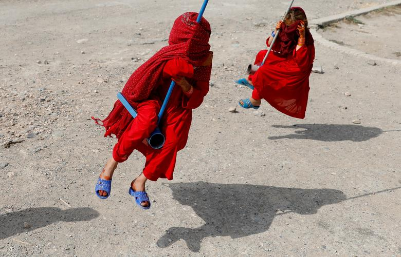 Afghan girls cover their faces as they ride on swings during the first day of the Muslim holiday of the Eid al-Adha, in Kabul, Afghanistan.  REUTERS/Mohammad Ismail