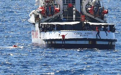 Migrants jump off stranded rescue ship