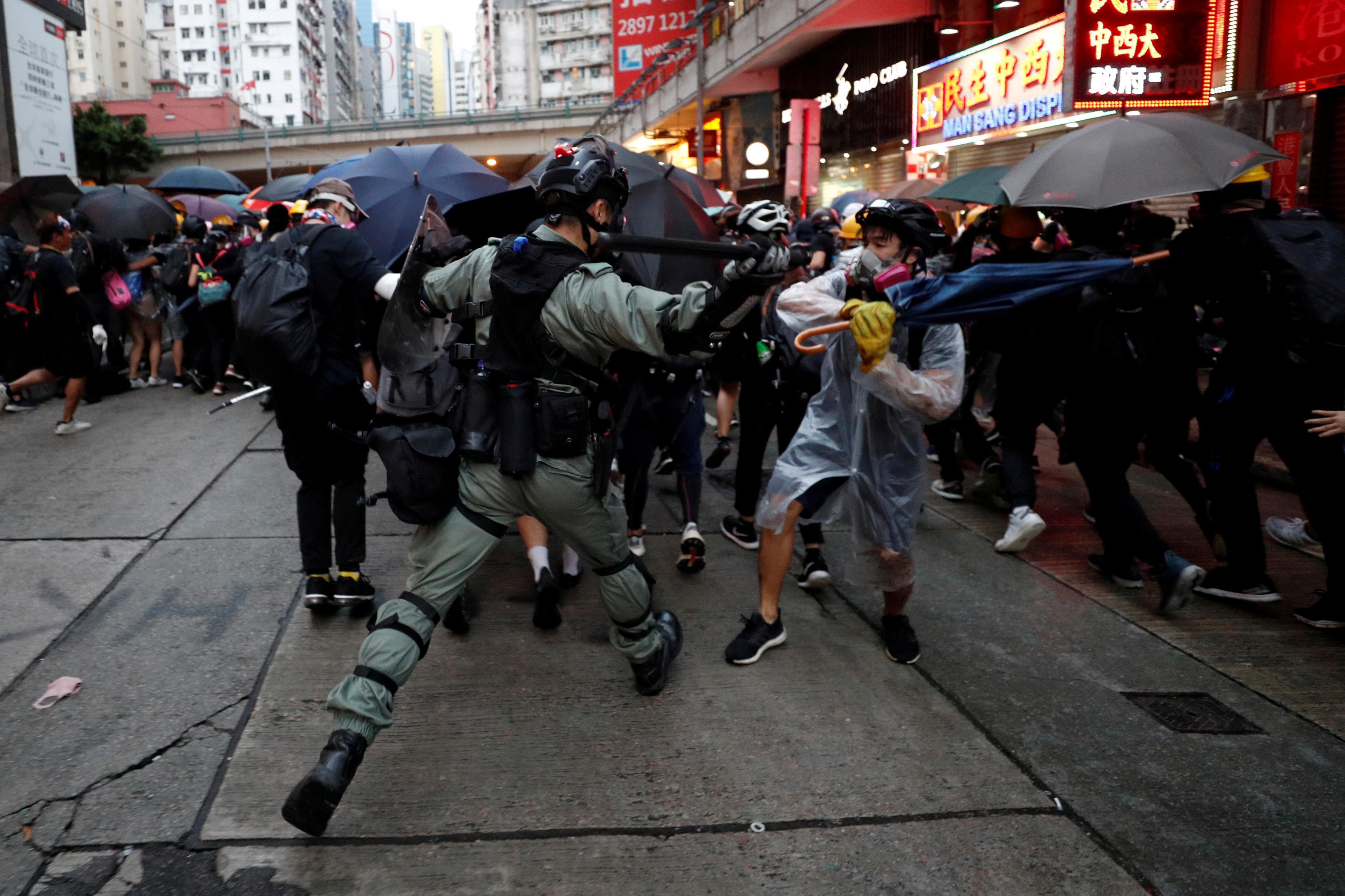 La police de Hong Kong fait une démonstration de force dans les rues, harcelée par les habitants
