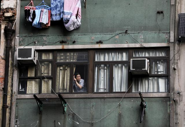A woman looks out of a window during an anti-government protest in Hong Kong, China, October 20, 2019. REUTERS/Ammar Awad