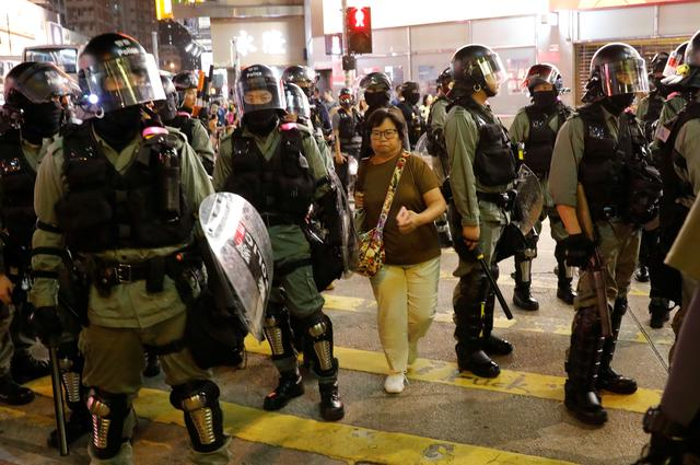 A woman makes her way between riot police officers as they try to disperse protesters gathering for a demonstration in Hong Kong, China, October 21, 2019. REUTERS/Kim Kyung-Hoon