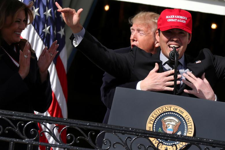 """President Donald Trump embraces catcher Kurt Suzuki as he welcomes the MLB World Series champion Washington Nationals to the White House in Washington, November 4, 2019. Popular Nationals players praised Trump at the White House celebration, days after the president drew boos from fans and criticism from pitcher Sean Doolittle. Trump wrapped Suzuki in a tight hug from behind when the catcher donned a red """"Make America Great Again"""" cap and said, """"I love you all. Thank you."""" REUTERS/Jonathan Ernst"""