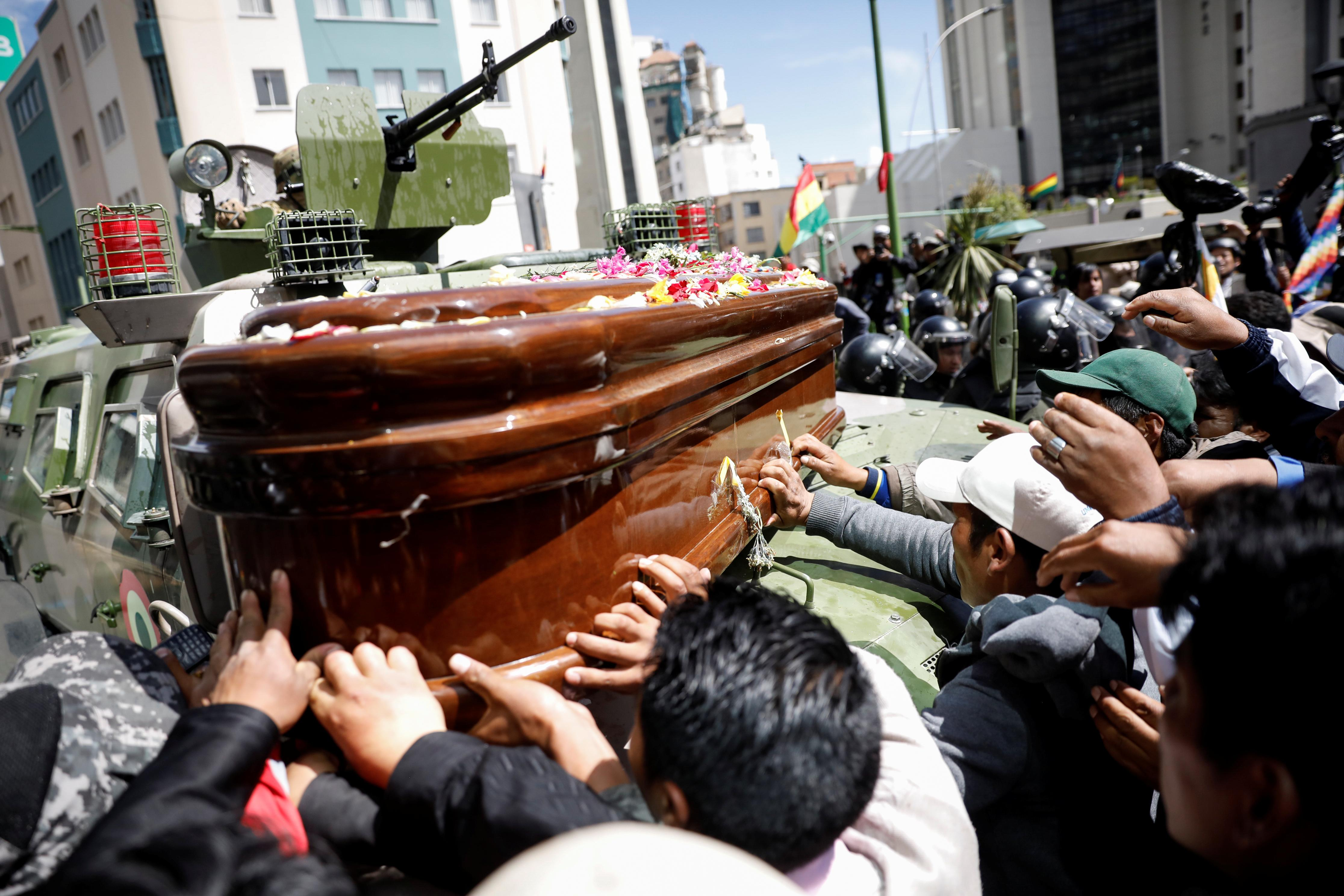 Supporters of Bolivia's Morales march with coffins of dead protesters