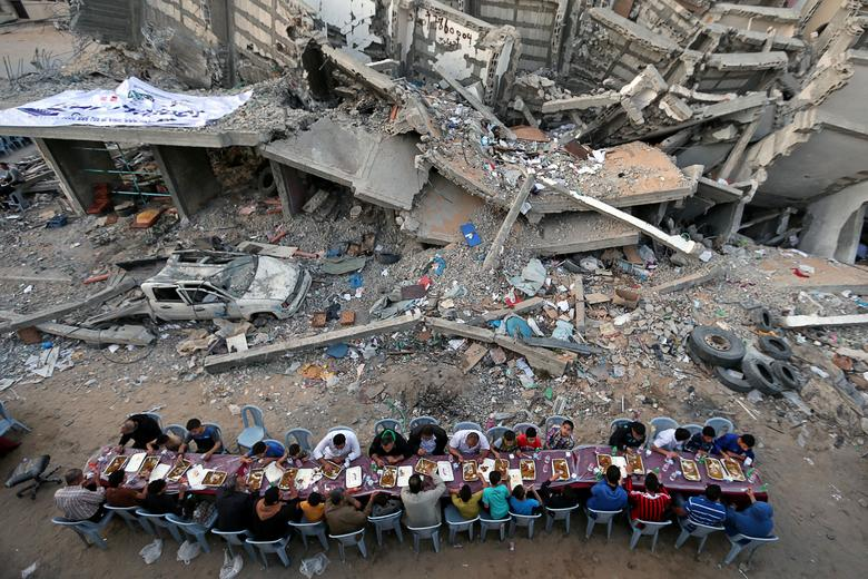 Palestinians break their fast by eating iftar meals during the holy month of Ramadan, near the rubble of a building recently destroyed by Israeli air strikes, in Gaza City, May 18, 2019. REUTERS/Ibraheem Abu Mustafa