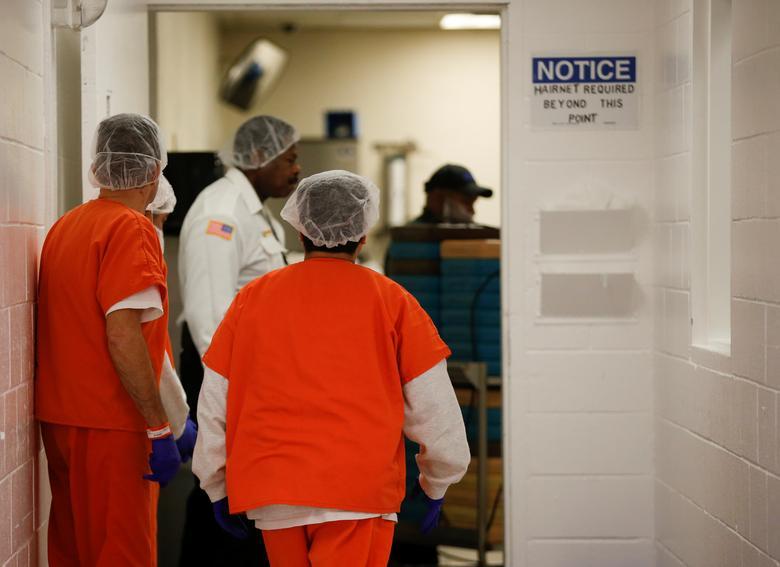 Los detenidos usan redecillas para el cabello mientras esperan que los carritos de bandejas de comida se entreguen durante un recorrido por los medios en el Centro de Procesamiento de Northwest ICE. REUTERS / Lindsey Wasson