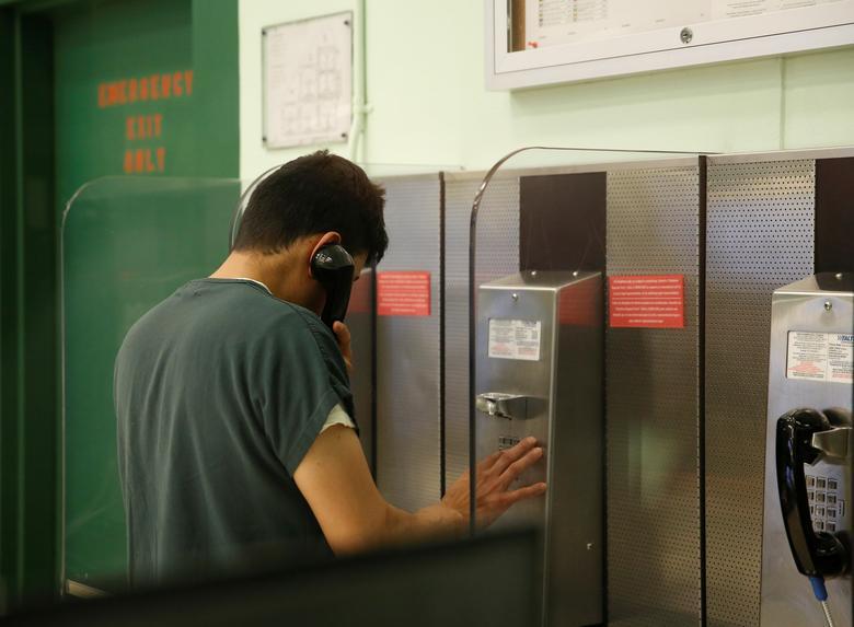Un detenido usa un teléfono en su unidad de vivienda durante una gira de medios en el Centro de Procesamiento de Northwest ICE. REUTERS / Lindsey Wasson
