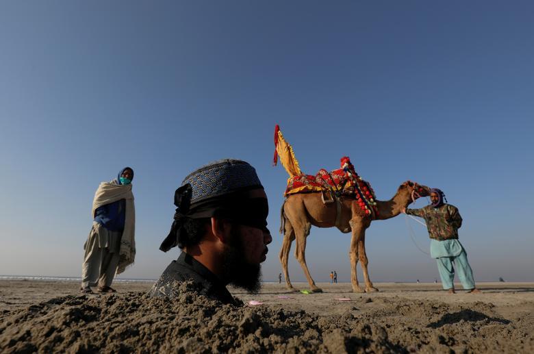 Mehrban Akhtar, de 20 años, con los ojos vendados y enterrado hasta el cuello en la arena durante un eclipse solar, es fotografiado a lo largo de la playa de Clifton en Karachi, Pakistán, el 26 de diciembre de 2019. Muchos pakistaníes creen que enterrar a las personas con discapacidad en la arena durante el eclipse solar traería curación a sus cuerpos.  REUTERS / Akhtar Soomro