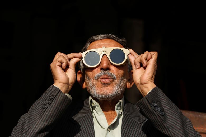 Un hombre usa un par de lentes de soldador para observar un eclipse solar en Peshawar, Pakistán, 26 de diciembre de 2019. REUTERS / Fayaz Aziz