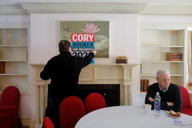 FILE PHOTO: A volunteer places a poster for Democratic 2020 U.S. presidential candidate and U.S. Senator Cory Booker (D-NJ) at a campaign stop in Rochester, New Hampshire, U.S., February 17, 2019.   REUTERS/Brian Snyder/File Photo