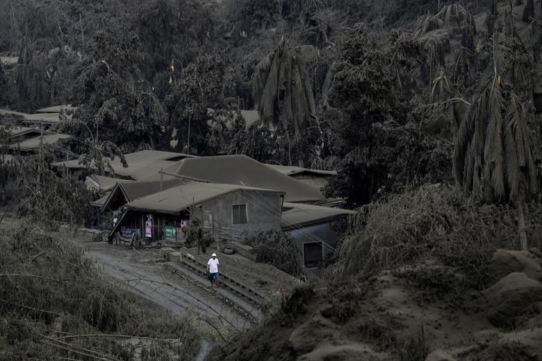Un hombre camina en una carretera cubierta de cenizas del volcán Taal en erupción en Talisay, Batangas, Filipinas, el 13 de enero. REUTERS / Eloisa Lopez
