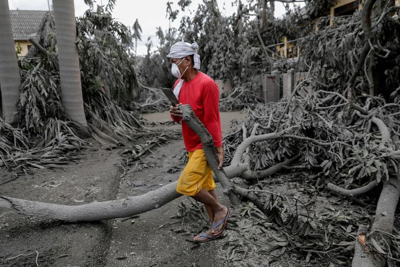 Un trabajador lleva una rama caída en un complejo cubierto de cenizas volcánicas en Talisay, Batangas, Filipinas, el 14 de enero. REUTERS / Eloisa Lopez