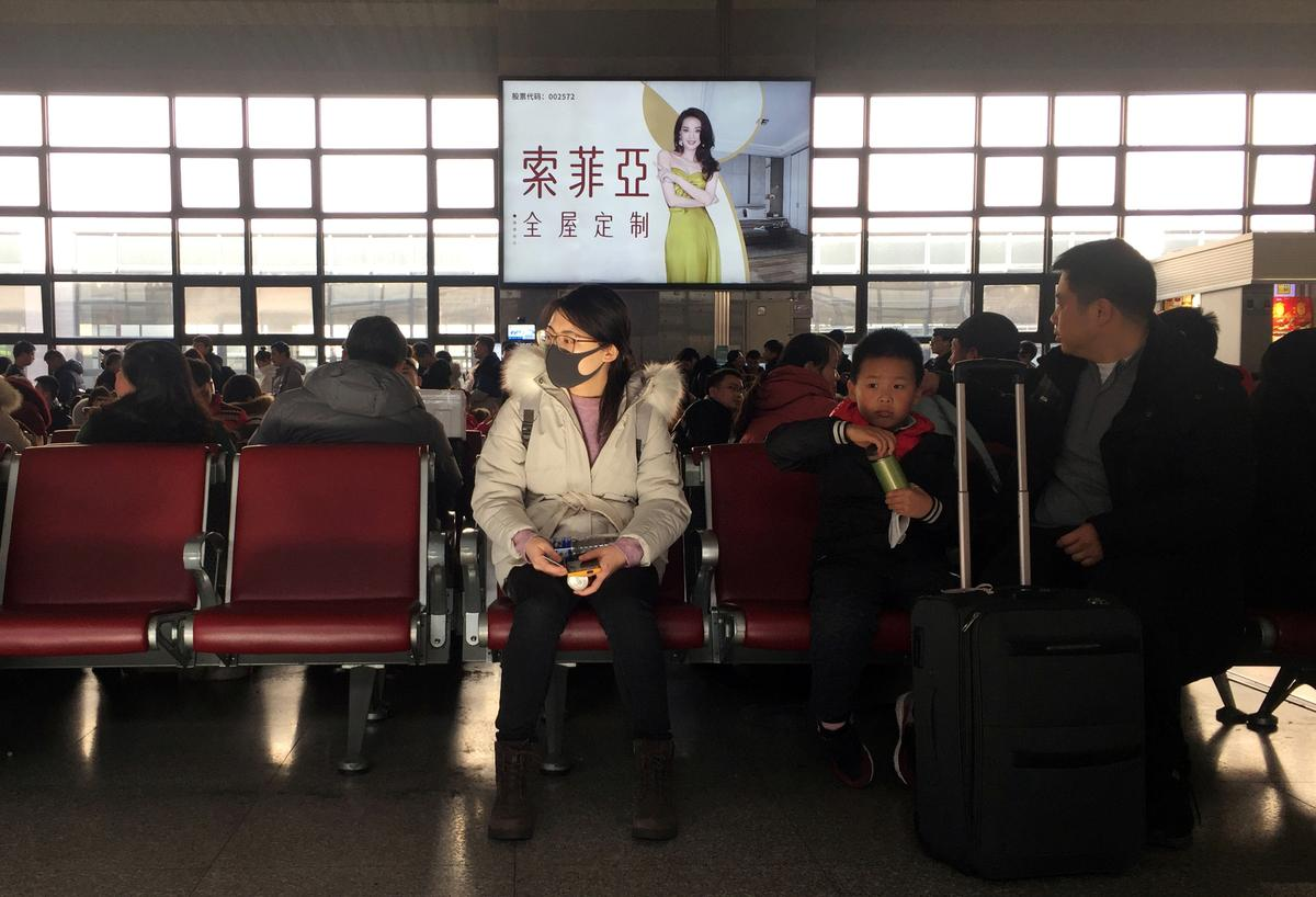 Masks on, Chinese start holiday travels as alarm mounts over mystery virus