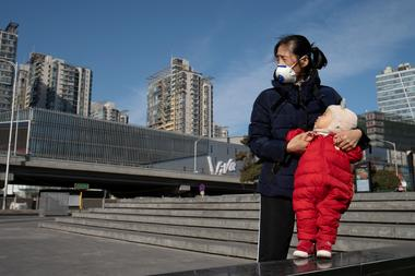 Woman wearing a face mask holds a child near a shopping mall in Beijing