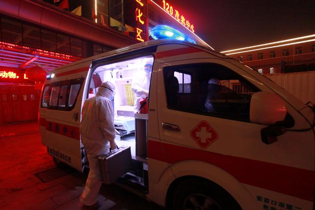 A medical worker in protective suit gets onto an ambulance at a hospital, following an outbreak of the novel coronavirus in the country, in Xuanhua district of Zhangjiakou, Hebei province, China February 13, 2020.  China Daily via REUTERS