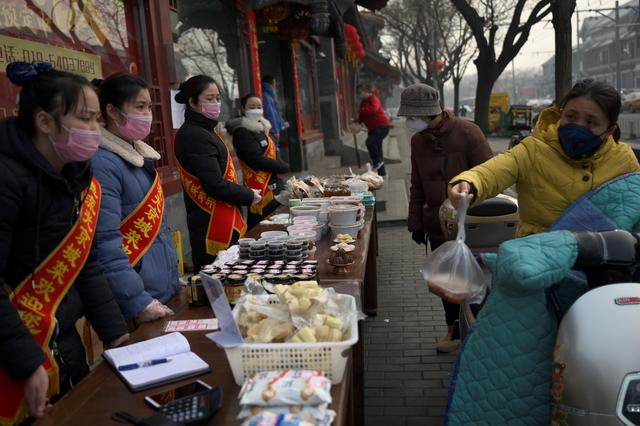 People wearing face masks buy food from a stall set up by a restaurant in Beijing, following an outbreak of the novel coronavirus in  China, February 13, 2020. REUTERS/Tingshu Wang