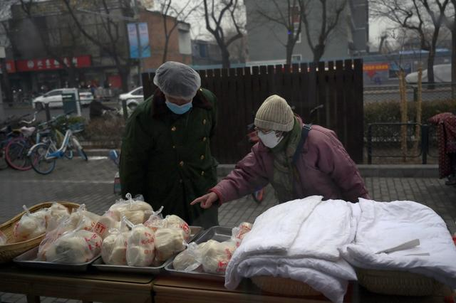 A woman wearing a face mask buys food from a stall set up by a restaurant outside its outlet in central Beijing, following an outbreak of the novel coronavirus in China, February 13, 2020. REUTERS/Tingshu Wang